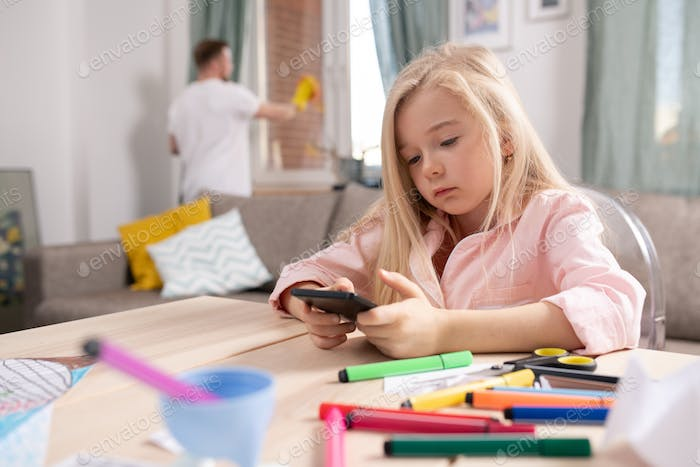 Little restful blond girl scrolling in smartphone while sitting in living-room