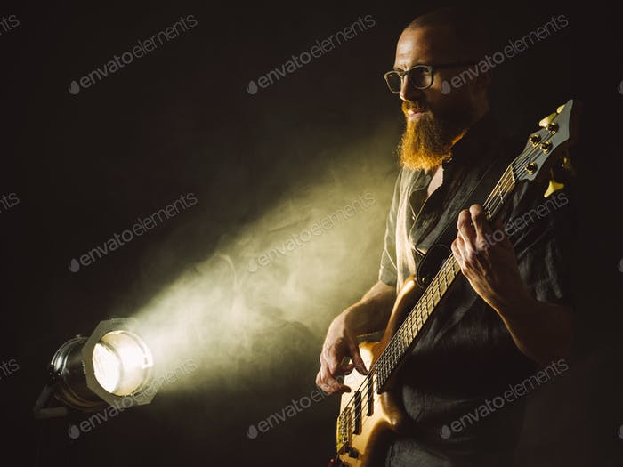 Bearded man playing bass guitar with spotlight