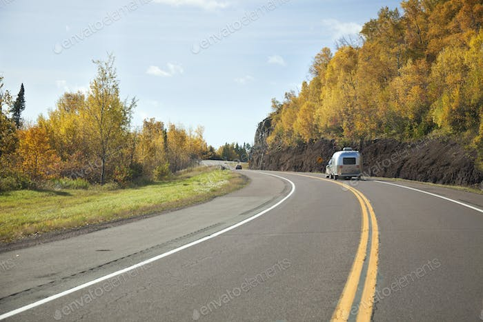 Camper travels by hills in fall color on the north shore of Lake Superior in Minnesota