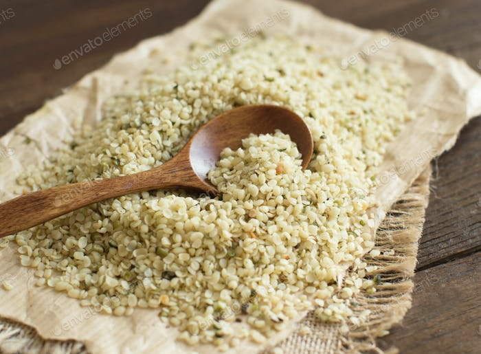 Hemp seeds with a spoon on wood