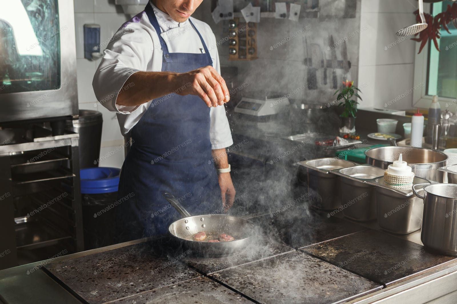 Chef cooking meat at restaurant or hotel kitchen