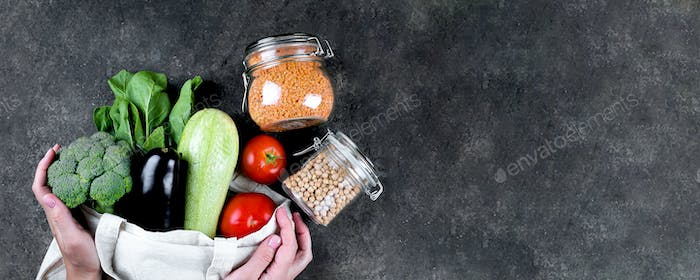 Zero waste concept. Female hands holding vegan vegetables in reusable bag, glass jars with chickpea