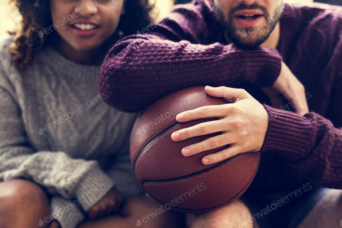 Young couple watching basketball match at home