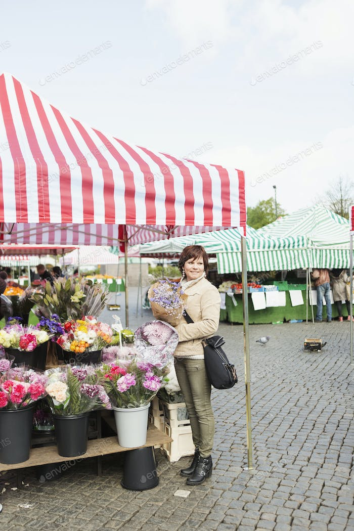Happy mature woman buying bouquet at flower stall