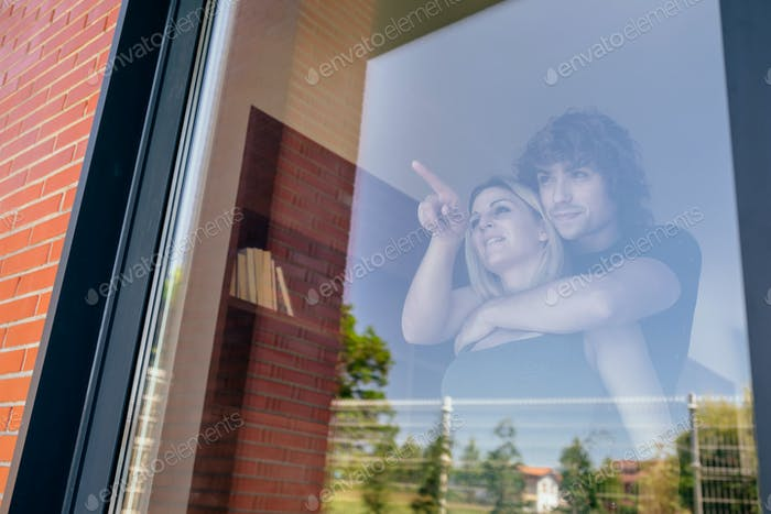 Paar blickt durch das Fenster in den Garten