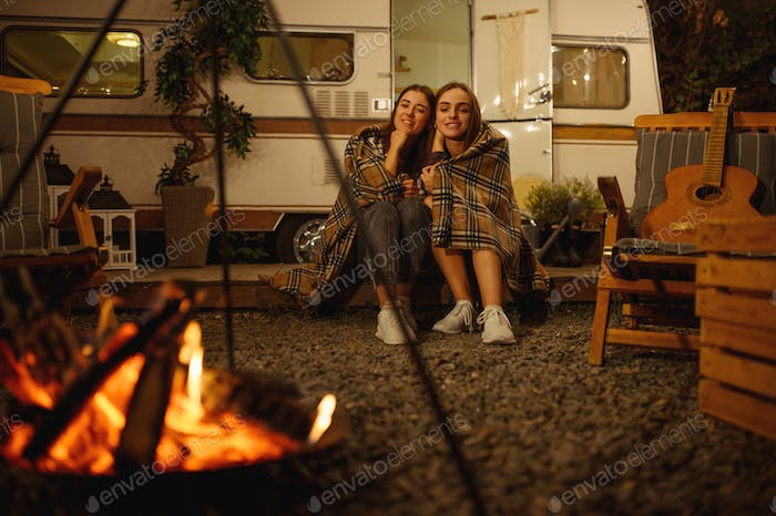 Girlfriends wrapped in plaid sitting by campfire