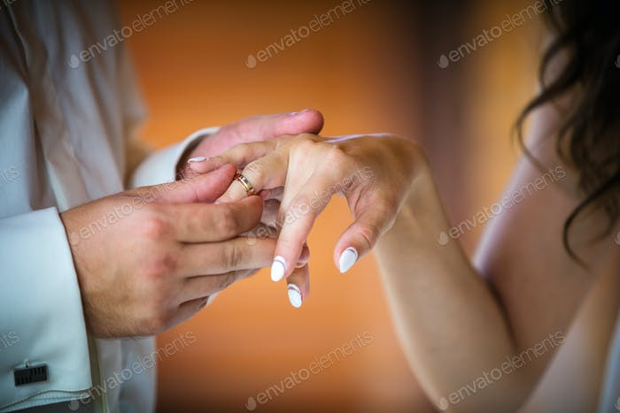 Groom putting ring on bride's finger, cropped view indoors
