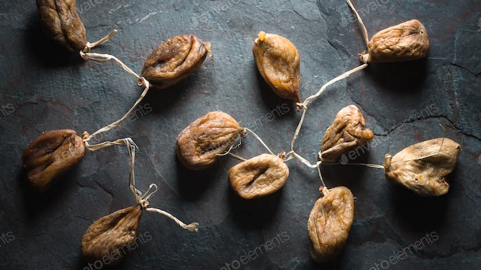 Dried beige figs with a string on a gray stone