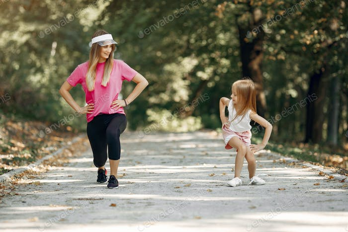 Mother with daughter doing sport in a summer park