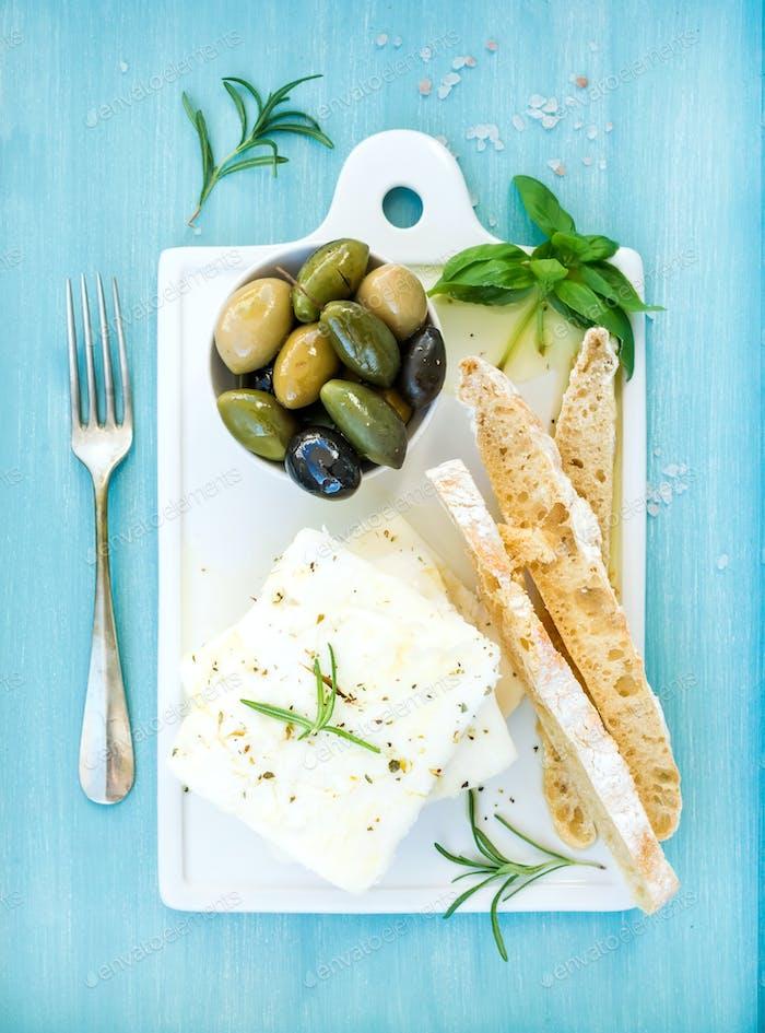 Frischer Feta-Käse mit Oliven, Basilikum, Rosmarin und Brotscheiben