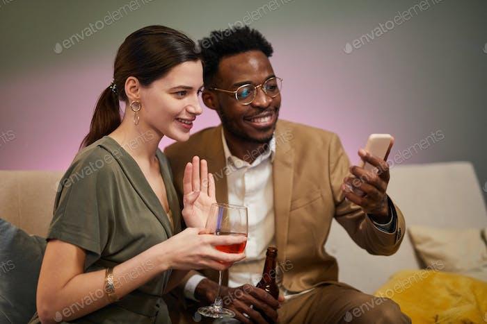 Paar winkt Hallo zum Videochat