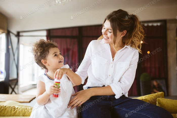 Young mother in white shirt and little cute daughter in dress ha