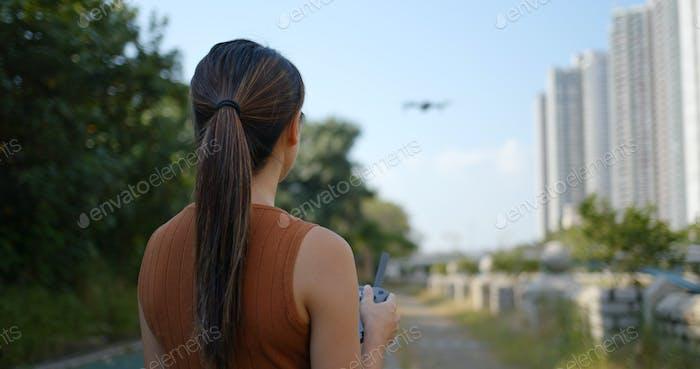 Frau spielen mit fliegenden Drohne im freien