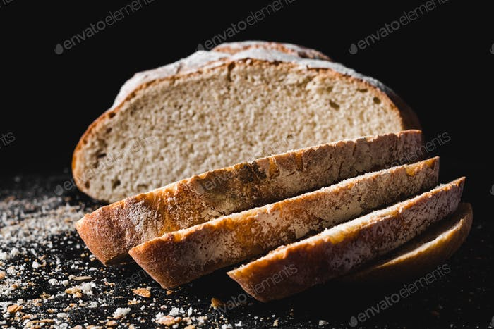 Sliced loaf of dark homemade bread dusted with flour