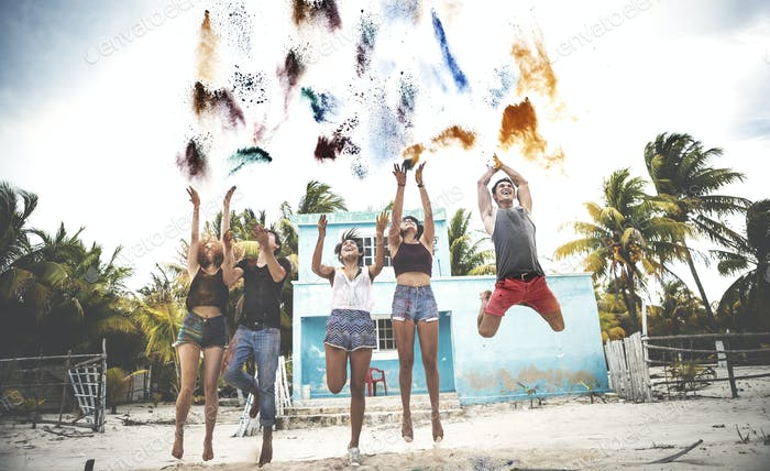 Young people standing on a beach throwing paint pigment into the air.