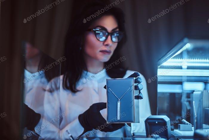 Assistent zeigt die exklusive Goldkette im Luxusjuwelier