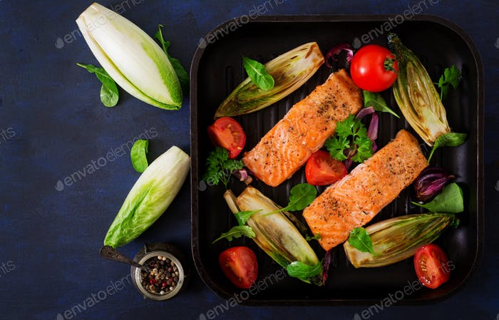 Baked salmon with Italian herbs and garnished with chicory. Top view.
