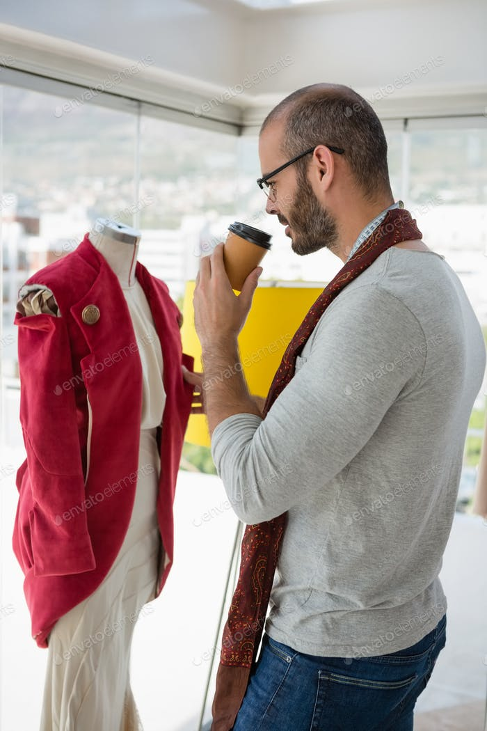 Designer examining clothes while drinking coffee