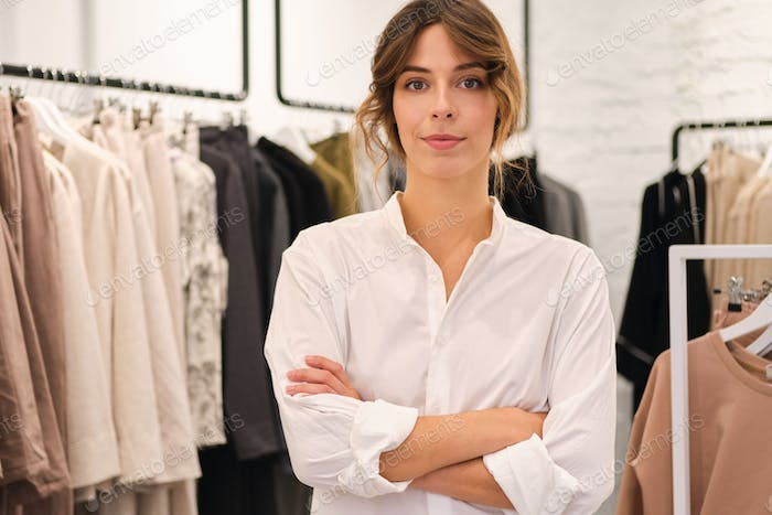 Young attractive woman in shirt holding hands crossed confidently looking in camera in clothes store