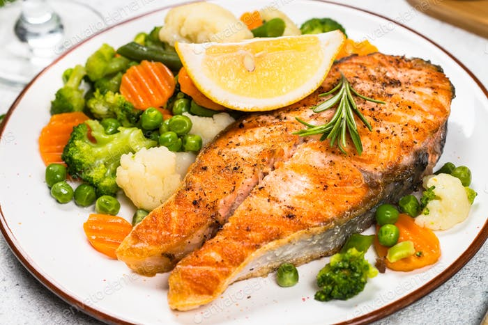 Grilled salmon steak with vegetables on white