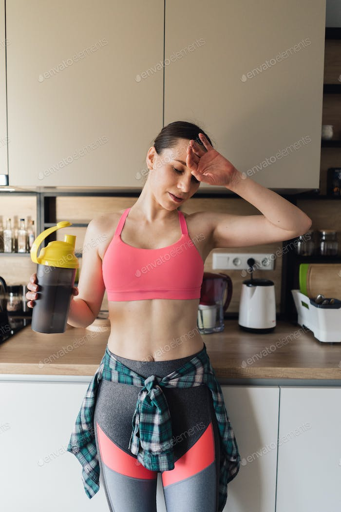 Delighted woman drinking water after workout at home