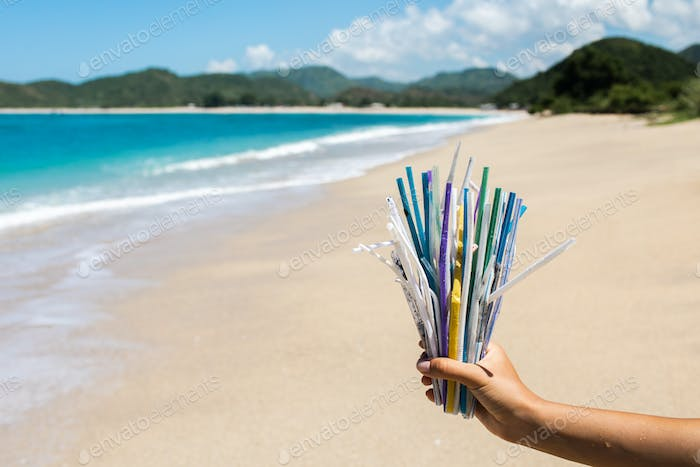 Hand holding heap of used plastic straws on background of clean tropical beach and ocean waves