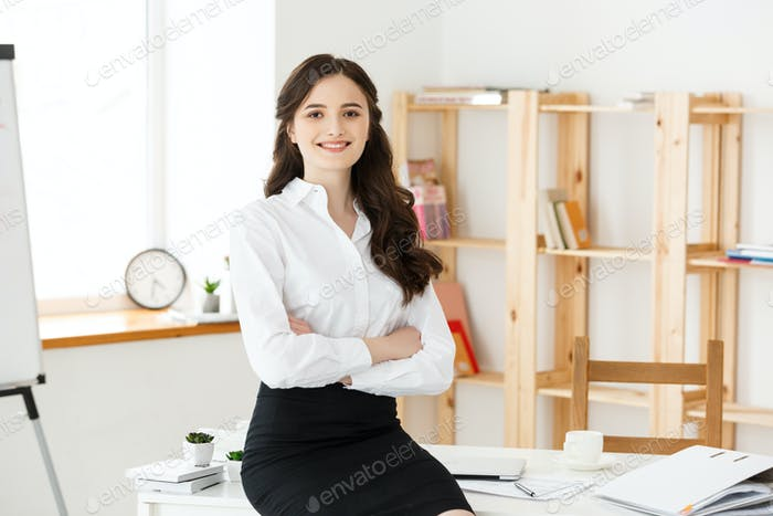 Smiling mature professional businesswoman with arms crossed sitting on the desk in office