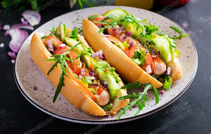Hot Dog mit Wurst, Gurke, Tomaten und roten Zwiebeln auf dunklem Hintergrund.