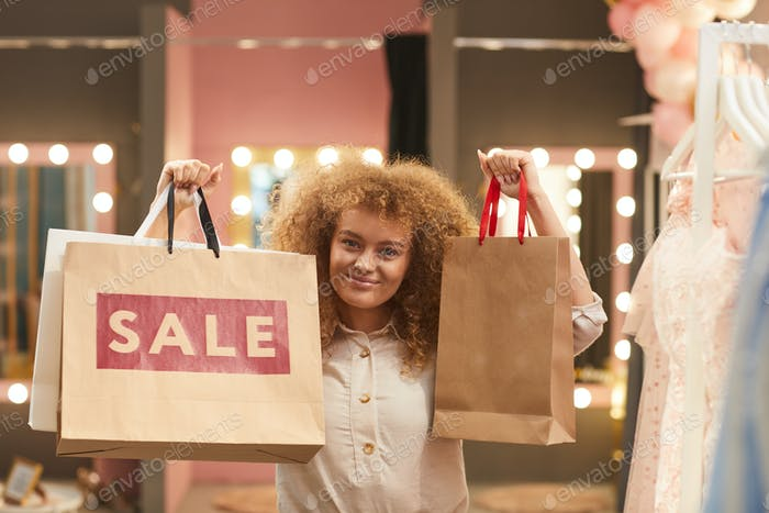 Happy Young Woman Holding Shopping Bags in Boutique