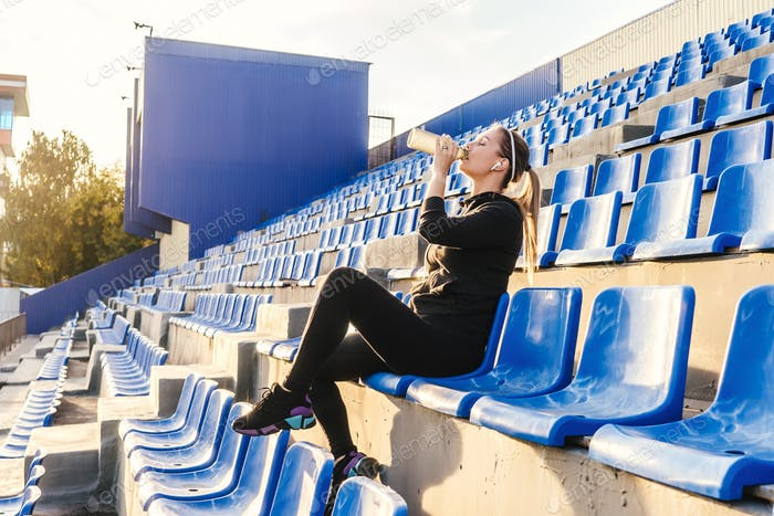 Fitness woman sit on stadium tribune.