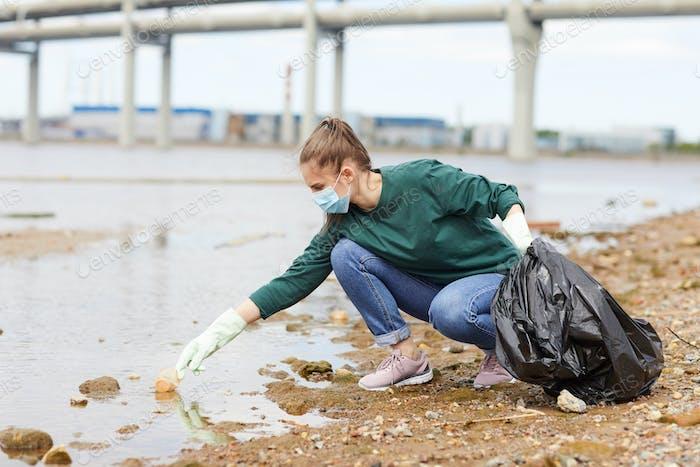 Mujer limpiando el río en la ciudad