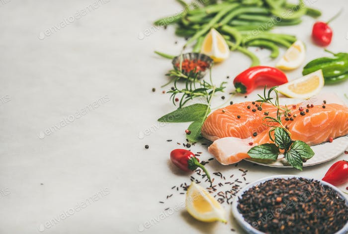 Raw salmon steaks with vegetables, greens and rice, copy space