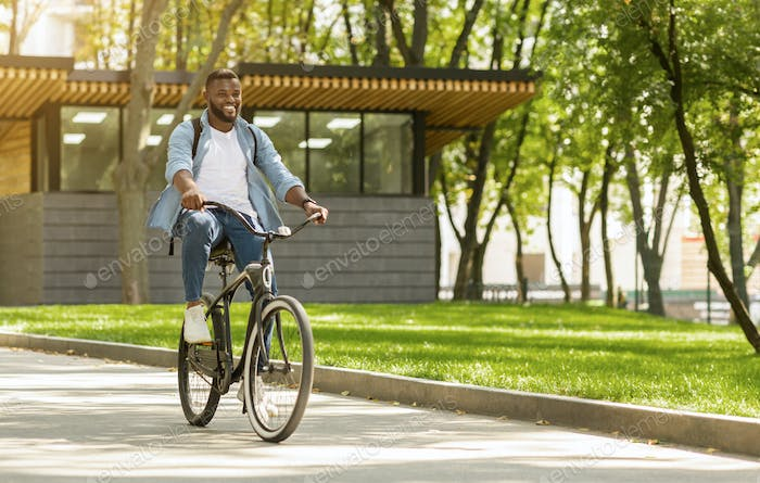 Eco Ride. Happy african american man riding bicycle in city
