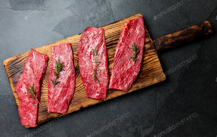 Beef tenderloin on wooden board, spices, herbs, oil on slate gray background
