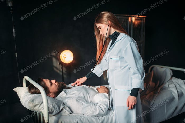Female doctor listens to the heart of male patient