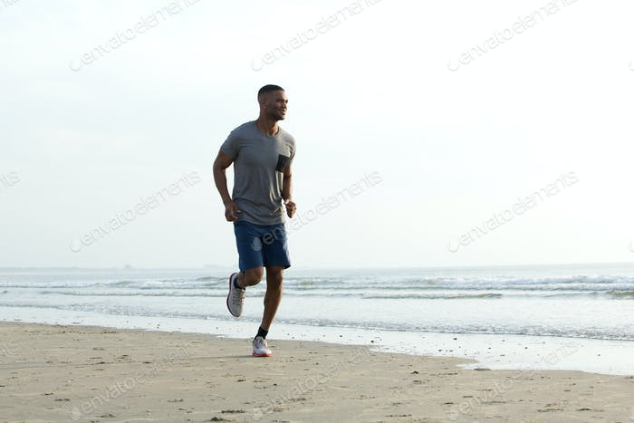 Young african man jogging at the beach