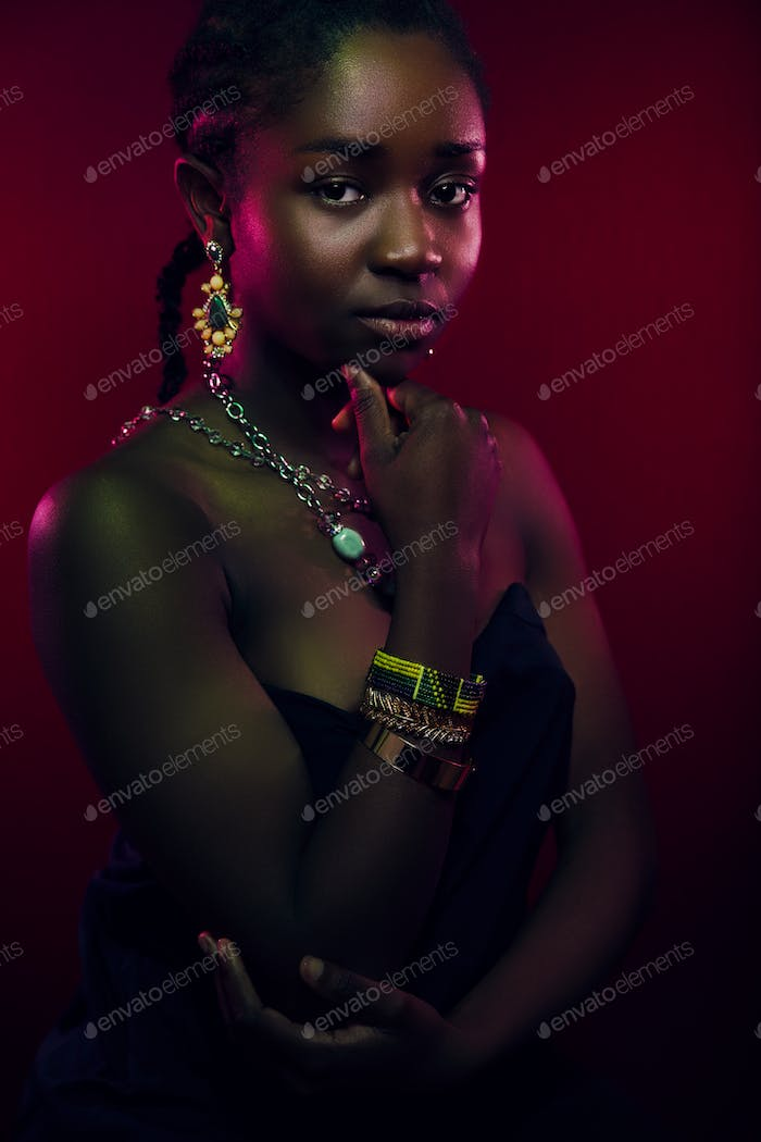 Colorful portrait of sensuous woman wearing jewelry over red background