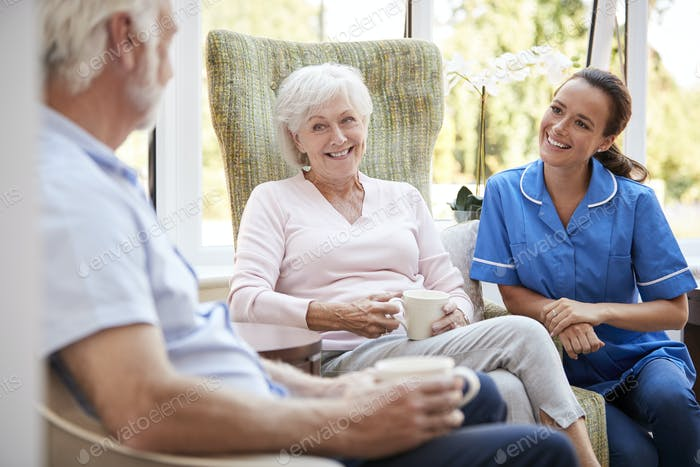 Senior Couple Sitting In Chair And Talking With Nurse In Retirement Home