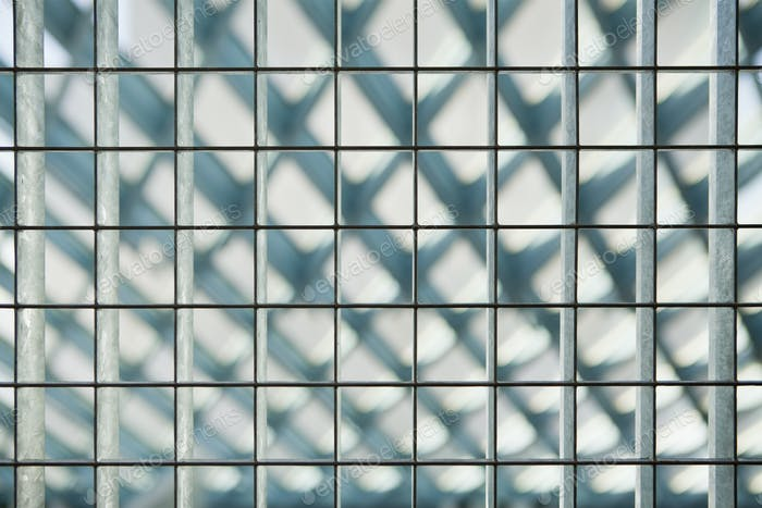 Grid pattern, barrier with square metal shapes, diamond shape blurred background.