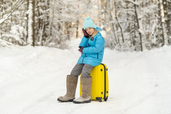 A girl in winter in felt boots sits on a suitcase on a frosty snowy day