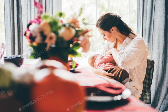 Young woman with long dark hair breastfeeding baby