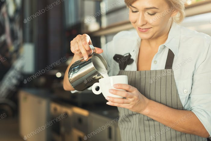 Experienced barista pouring milk to cappuccino cup