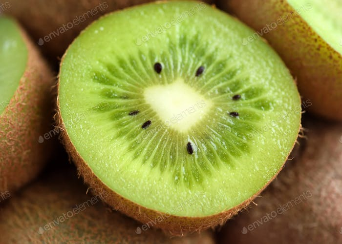 Slices of kiwi fruit on kiwi background