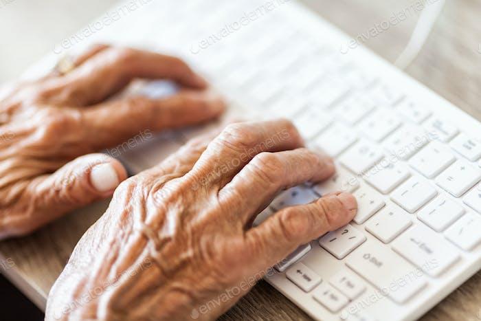 Mujer mayor escribiendo en un teclado