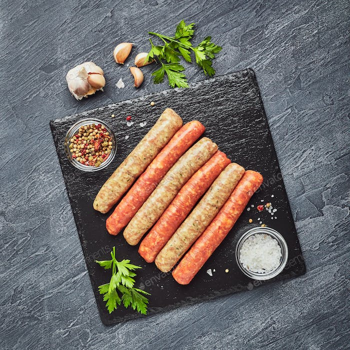 Raw butchers sausages on slate with herbs. Overhead view