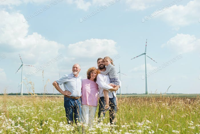 Multigeneration family standing on field on wind farm.
