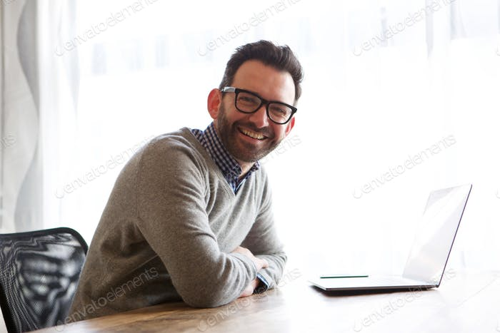 happy businessman smiling with laptop