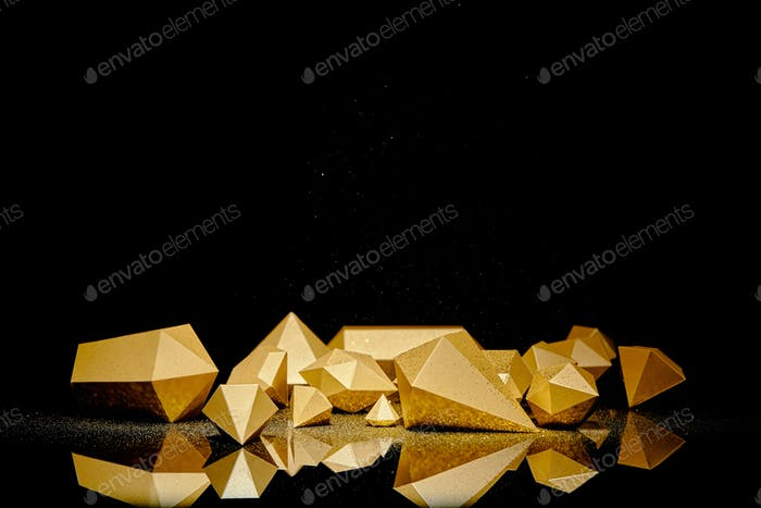 glänzende facettierte goldene Stücke und Staub spiegeln sich auf schwarzem Hintergrund