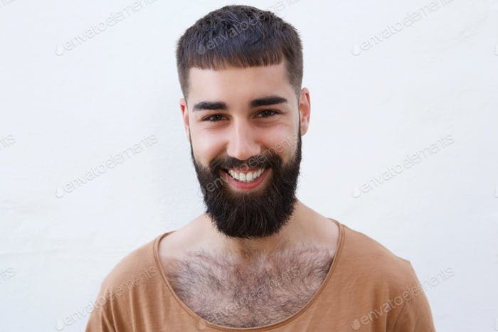 Happy confident man with beard standing by wall