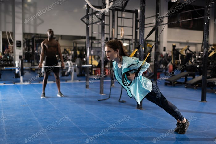 Woman doing TRX exercises and man training with barbell in gym